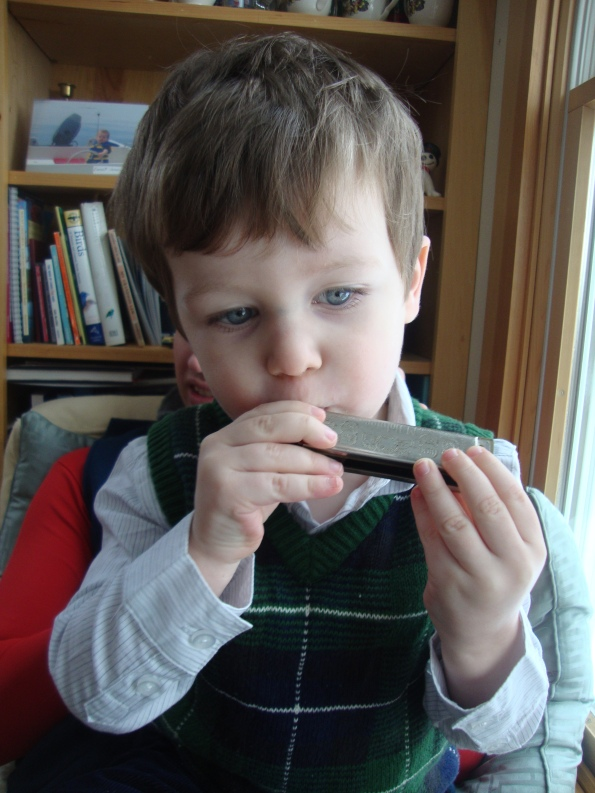 toddler playing harmonica